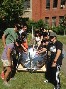Grad students and Johnson interns next to parabolic solar dish